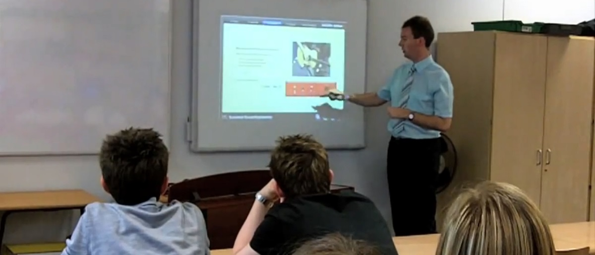teacher using Sounds Active to demonstrate mic technique on a smart board